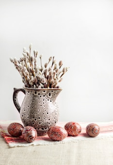 Pâques nature morte avec pysanka et branches de saule dans une cruche en céramique sur un tissu ukrainien traditionnel. oeufs de pâques décorés, traditionnels pour la culture de l'europe de l'est