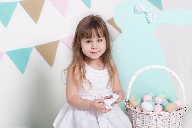 Pâques. petite fille vêtue d'une robe blanche est assise près d'un panier avec des œufs et un lapin de pâques. lieu de pâques coloré, décor de printemps. vacances en famille, traditions. petit fermier. récolte. fête