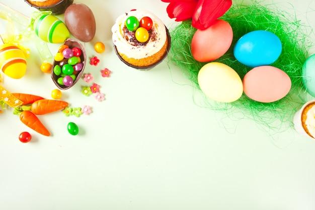 Pâques sertie d'oeufs colorés, carottes, bonbons, cupcake. vue de dessus. copiez l'espace.