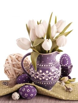 Pâques avec des tulipes blanches dans un pichet violet et des œufs de pâques assortis