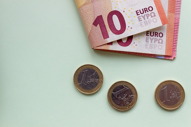 Un paquet de 10 billets et pièces en euros sur une surface claire