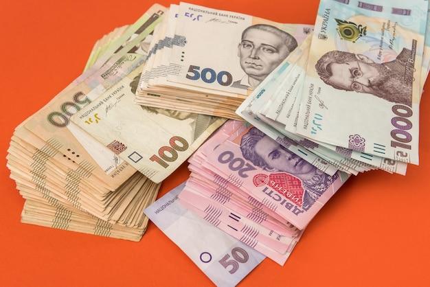 Paquet d'argent ukrainien isolé sur rouge, pile de hryvnia uah, 200 500 et nouveau billet de 1000. notion d'argent