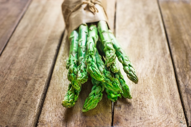 Paquet d'asperges organiques vertes brutes fraîches nouées avec de la ficelle sur la table de cuisine en bois de planche
