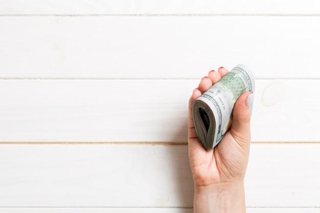 Un paquet de billets de cent dollars dans une main féminine sur fond en bois. concept de salaire avec espace de copie