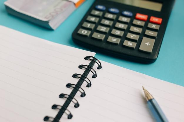 Paquet de billets en euros et une calculatrice sur fond bleu