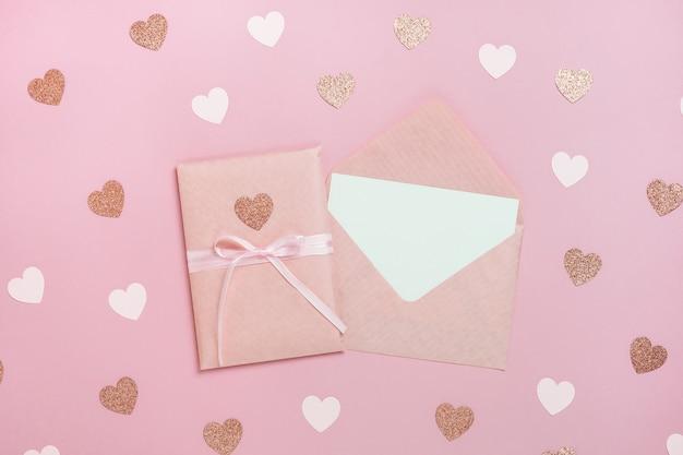 Paquet de boîte-cadeau avec ruban rose et enveloppe avec carte vierge sur fond rose pastel avec des coeurs