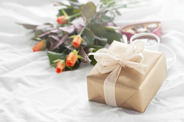 Paquet cadeau d'or avec un bouquet de fleurs et des chocolats