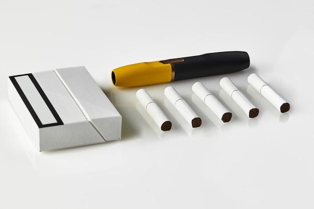 Paquet de cigarettes électroniques noir et jaune de nouvelle génération et cinq bâtons chauffants isolés sur un nouveau blanc ...