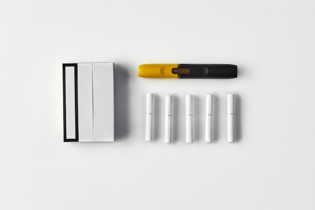 Un paquet de cigarettes électroniques noires et jaunes de nouvelle génération et cinq bâtons chauffants isolés sur blanc ...