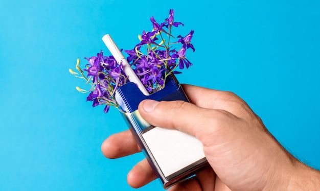 Paquet de cigarettes avec des fleurs à la main sur fond bleu