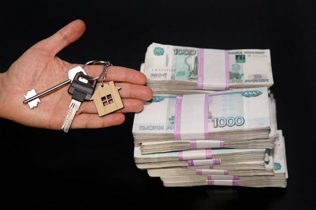 Un paquet de cinq mille billets avec les clés d'un appartement ou d'une maison sur fond blanc. acheter un bien immobilier pour de l'argent russe. opération immobilière