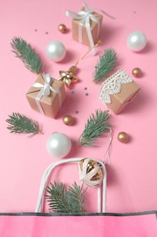 Paquet avec différentes décorations de noël sur fond rose. concept de nouvel an.