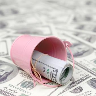Un paquet de dollars américains dans un seau en métal rose sur un ensemble de billets d'un dollar