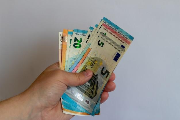 Un paquet d'euros dans les mains sur un fond blanc des billets en euros sur un fond blanc