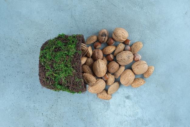 Paquet de noix sortant d'un bol de fantaisie sur le marbre.