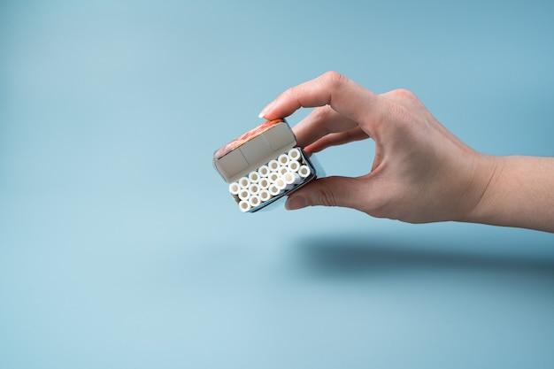 Un paquet ouvert de cigarettes dans la main d'une femme sur un fond bleu clair.