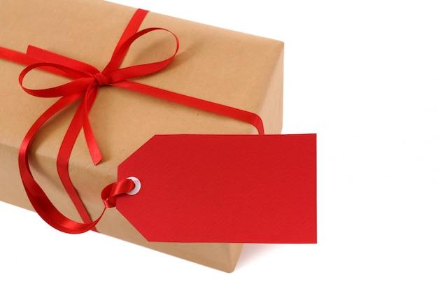 Paquet de papier brun attaché avec un ruban rouge et une étiquette cadeau.