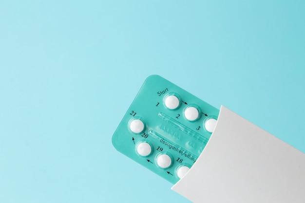 Paquet de pilules contraceptives orales avec instructions, blister dans un étui blanc sur bleu