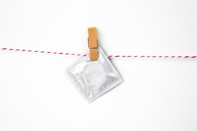 Paquet de préservatif sur une épingle à linge sur un fond blanc