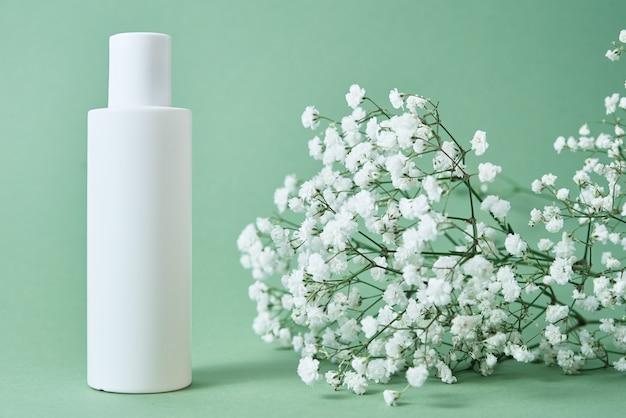 Paquet de produit beaty bouteille cosmétique sur fond vert pastel avec des feuilles de plantes cosmétiques maquette