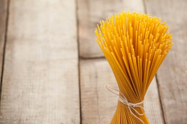Paquet de spaghettis crus attachés avec une corde sur une surface blanche