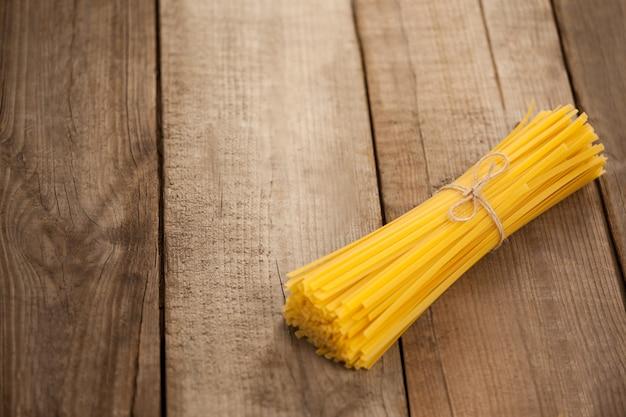 Paquet de spaghettis crus attachés avec une corde sur une surface en bois