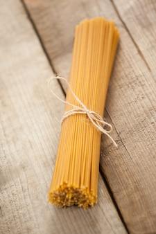 Paquet de spaghettis crus attachés avec un ruban blanc sur une surface en bois