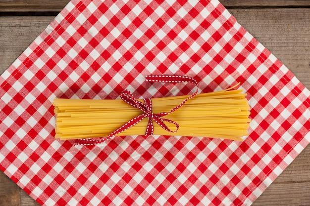 Paquet de spaghettis crus attachés avec un ruban rouge sur une serviette