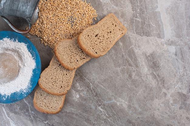 Paquet de tranches de pain, plateau de farine et pichet de blé renversé sur du marbre.