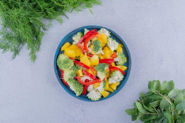 Paquets d'aneth et de menthe à côté d'un plateau de salade sur fond de marbre. photo de haute qualité