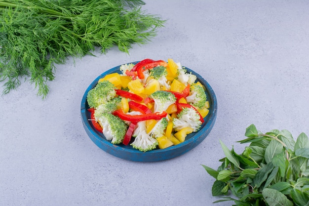 Paquets d'aneth et de menthe frais à côté d'un plateau de salades sur fond de marbre. photo de haute qualité