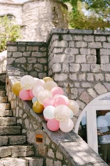 Des paquets de ballons à l'hélium aux couleurs rose pastel pour décorer une fête de mariage