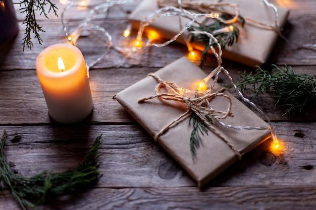 Paquets-cadeaux emballés dans du papier kraft, une bougie et de petites ampoules.