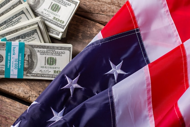 Paquets de dollars et drapeau américain. des paquets d'argent à côté du drapeau. richesse et opportunités. revenu du citoyen moyen.
