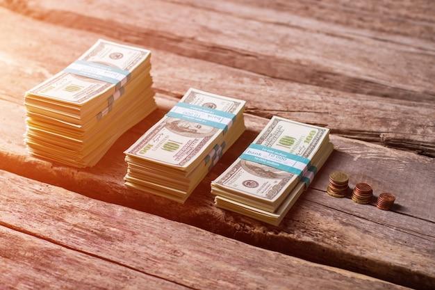 Paquets de dollars près des pièces de monnaie. petites pièces et espèces. argent sur une vieille étagère en bois. des haillons aux richesses.