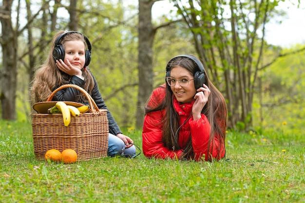Par une journée de printemps ensoleillée, deux sœurs dans le parc près du panier de pique-nique posé sur l'herbe et écouter de la musique