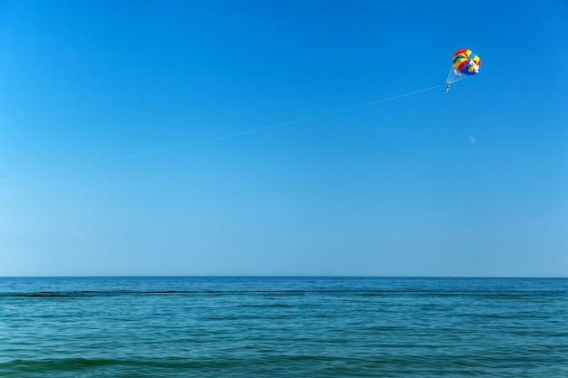 Parachute ascensionnel sur la mer, mer, ciel, activité, bleu, parachute, personnes, été, eau, voyage, divertissement, extérieur, air tropical, vent, extrême, voler avec un parachute derrière un bateau, personne, sport,
