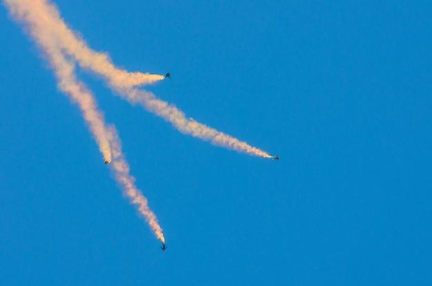 Les parachutistes quatre sautent avec de la fumée et volent dans le ciel bleu.