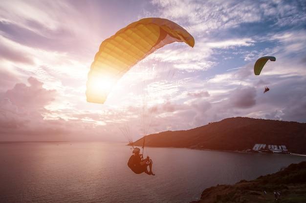 Paraglider chassant le coucher de soleil sur le point de vue du moulin à vent. phuket, thaïlande.