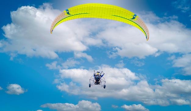 Paramoteur ou parapente motorisé sur le ciel avec fond de nuages