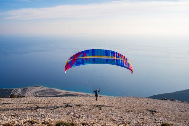 Le parapente commence le parachute se remplit d'air dans les alpes des montagnes par une journée ensoleillée en albanie
