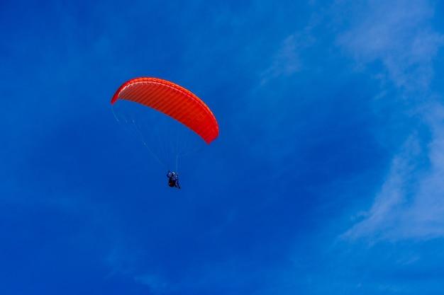 Parapente dans le ciel bleu. parachute avec parapente vole. sports extrêmes, concept de liberté