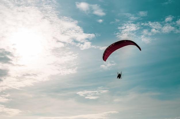 Parapente à moteur volant dans un ciel bleu avec un nuage blanc en arrière-plan.