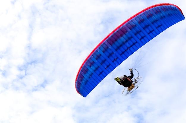 Parapente à moteur volant dans un ciel bleu avec un nuage blanc
