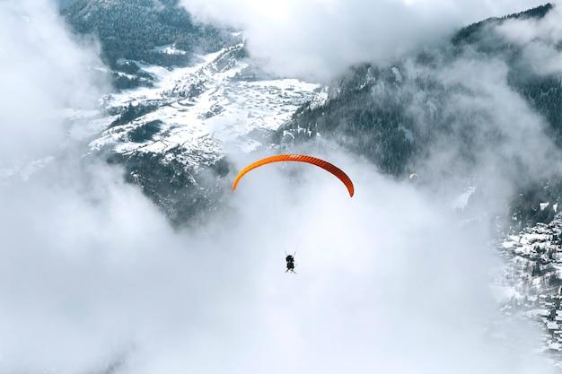 Parapente par temps nuageux à travers la montagne
