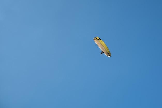 Parapente seul volant contre le ciel bleu. sports extrêmes - parapente dans le ciel sur fond de paysage magnifique avec une falaise de sable