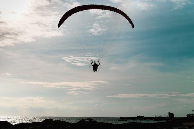 Parapente silhouette volant sur la mer dans le ciel turquoirs