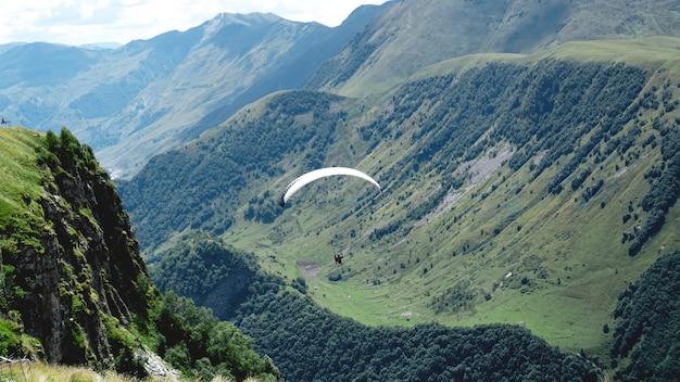 Parapente survolant les montagnes pendant la journée d'été - géorgie, kazbegi