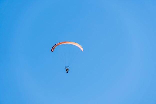 Parapente survolant la plage de saquarema, rio de janeiro. journée ensoleillée avec un ciel bleu en arrière-plan.