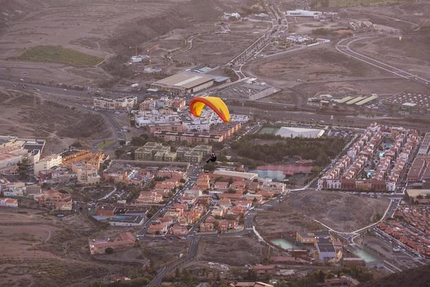 Parapente survolant le village d'adeje au sud de l'île de tenerife, dans les îles canaries, en espagne.